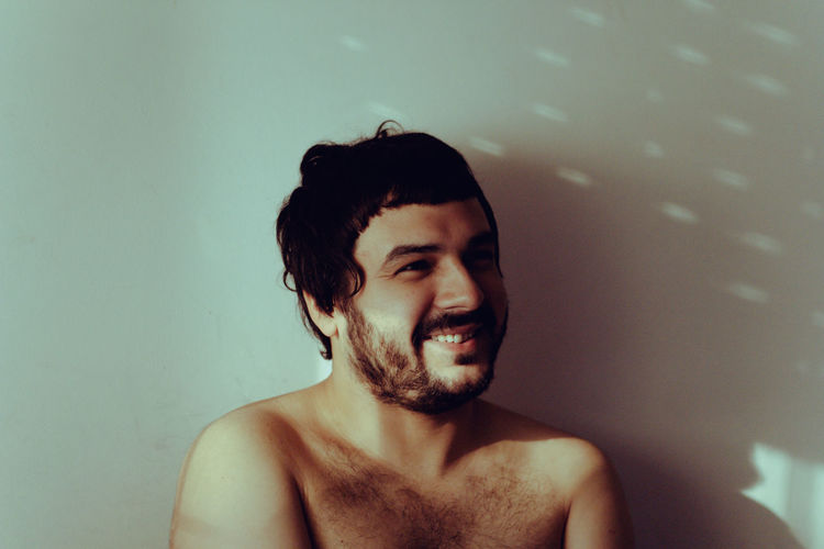 Close-Up Of Shirtless Young Man Smiling Against Wall