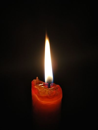 Close-up of burning candle against black background