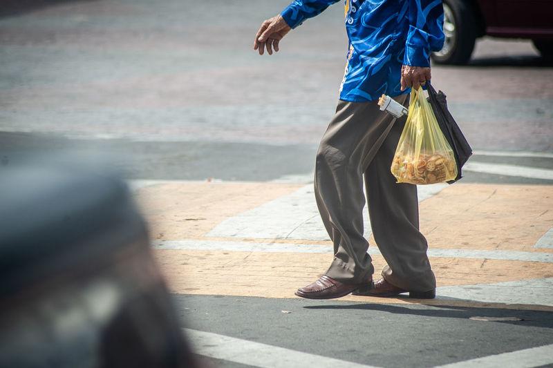 Low section of man walking on sidewalk