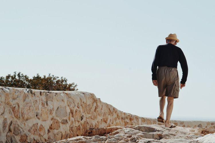 Rear view of man walking on rocks against clear sky