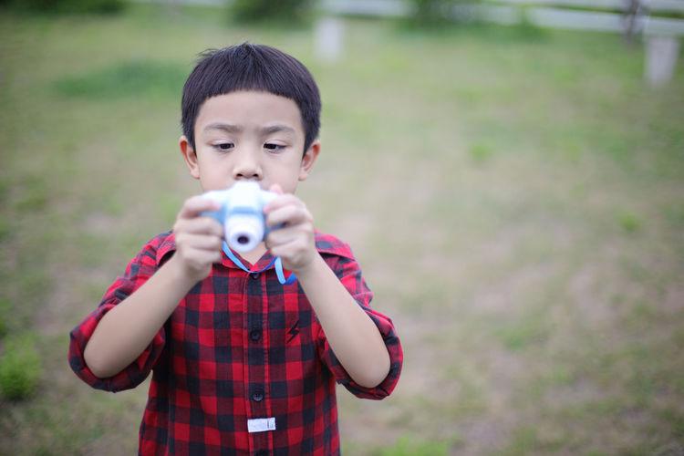 Portrait of cute boy holding camera