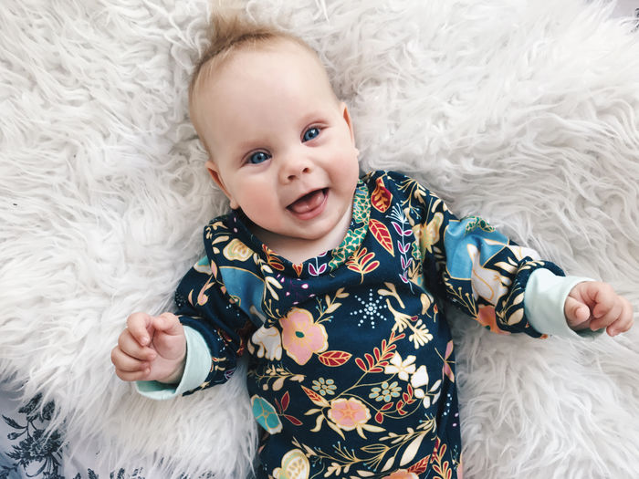 Portrait of cute baby girl on bed