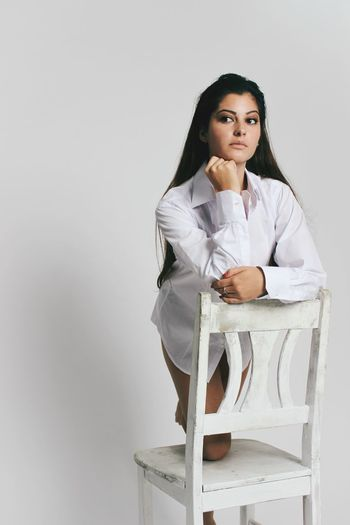 Woman Knelling On Chair Against White Background