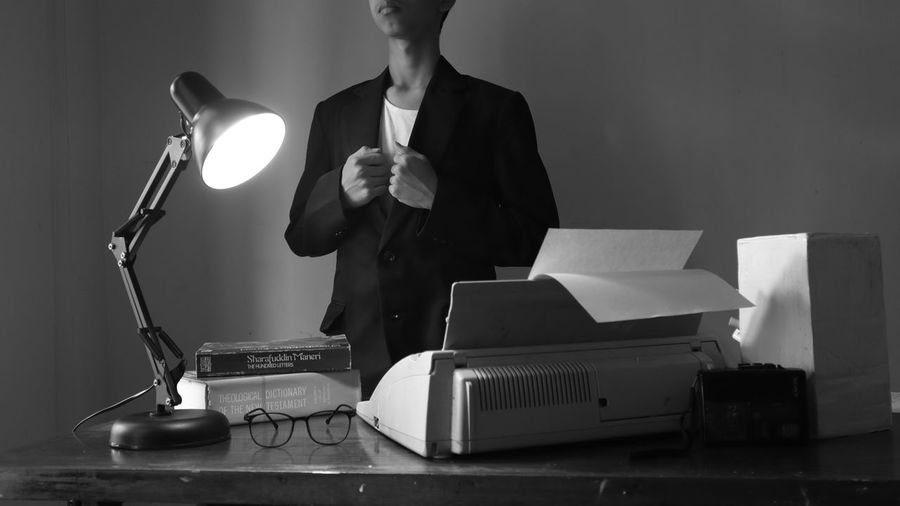 Midsection of businessman standing by book and lamp on table