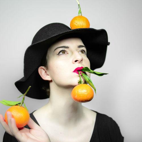 Portrait of woman holding apple against orange background