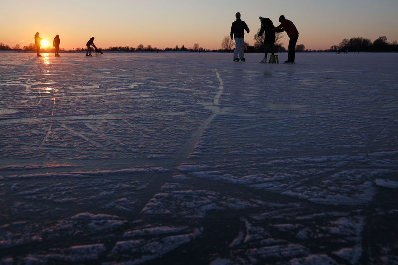 Silhouette people walking on snow covered land during sunset