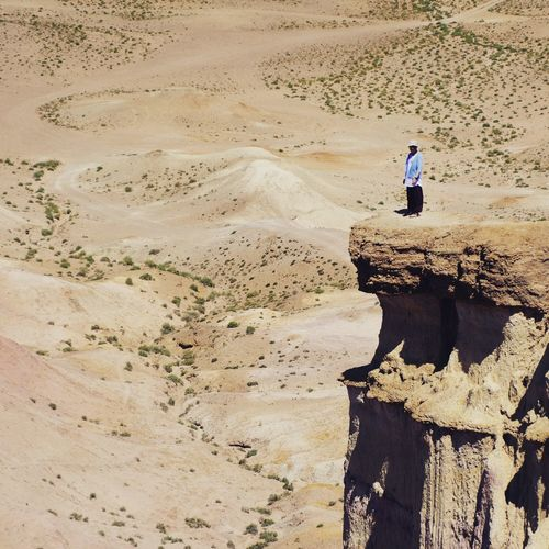 Mid Distance View Of Woman Standing On Cliff At Desert