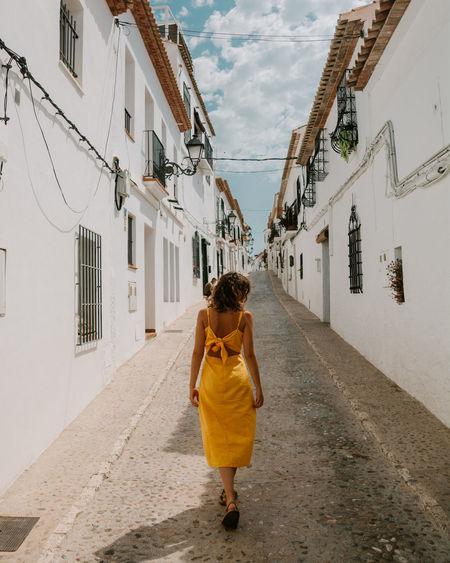 Woman walking on footpath in an alley