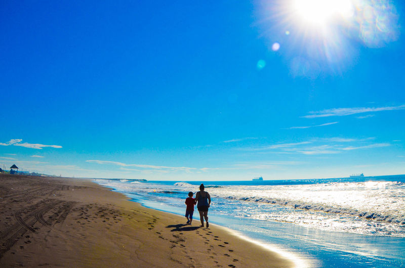 Rear view of mother and son walking at beach against blue sky during sunny day