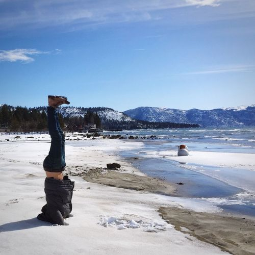 Man doing headstand in snow by sea against sky during sunny day
