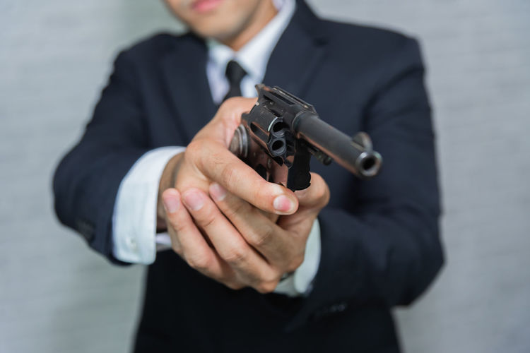 Midsection of businessman holding handgun while standing against wall