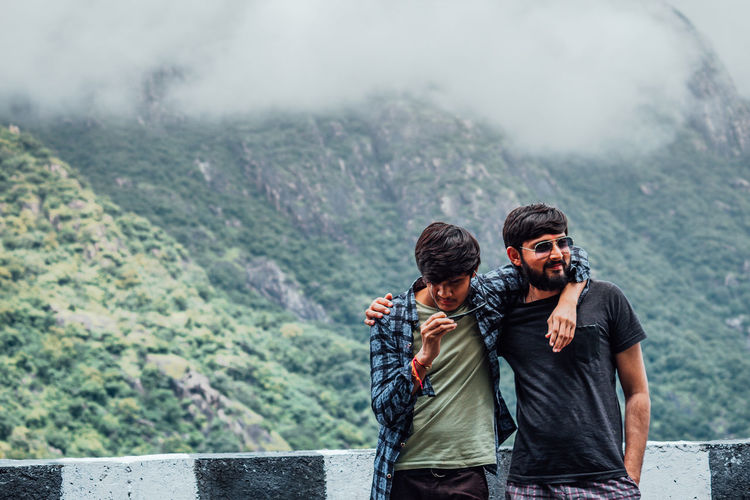 Friends standing against mountains