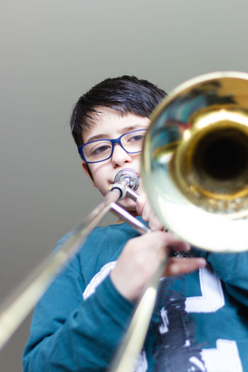 Portrait of cute boy playing trumpet against wall
