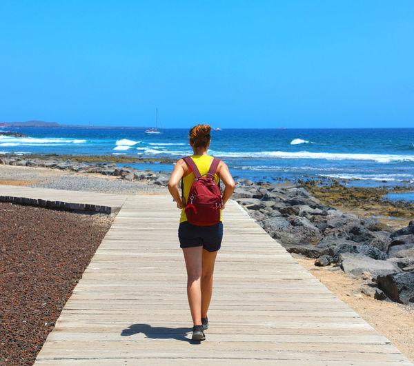 Rear view of woman walking on boardwalk at beach