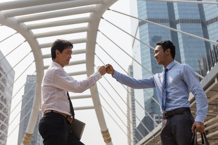 Low angle view of business people doing fist bump while standing on bridge