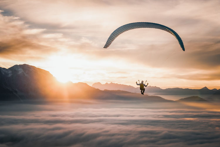 Paragliding pilot flying above sea of clouds at sunset, salzburg, austria.