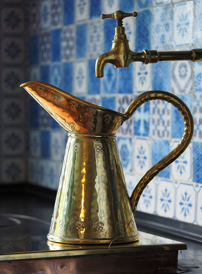 Antique metallic pitcher on table