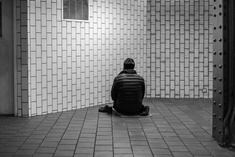 Rear view of a man sitting against the wall