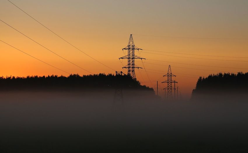 Low Angle View Of Silhouette Electricity Pylons Against Orange Sky In Foggy Weather