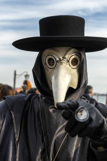 Close-up of man wearing costume against sky