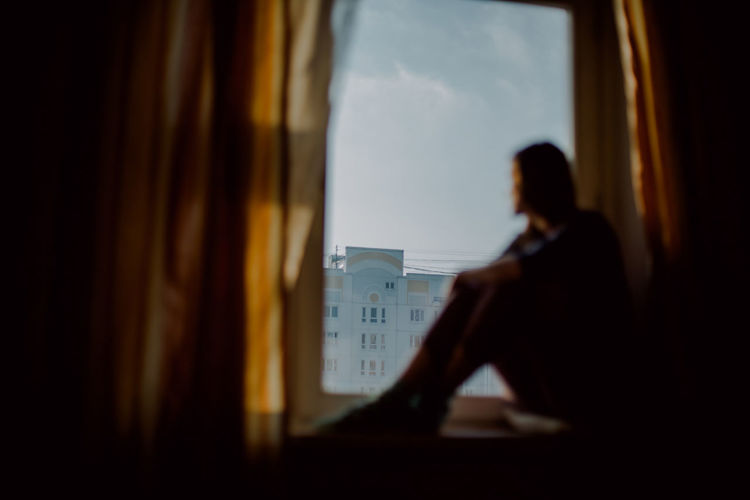 Profile Shot Of a Woman Sitting On Window Sill at a Sunset Time in the Background of a Panel Building in Moscow Window Sitting Indoors  One Person Adult Glass - Material Transparent Waist Up Men Travel Looking Journey Real People Public Transportation Day Transportation Selective Focus Mode Of Transportation Waiting