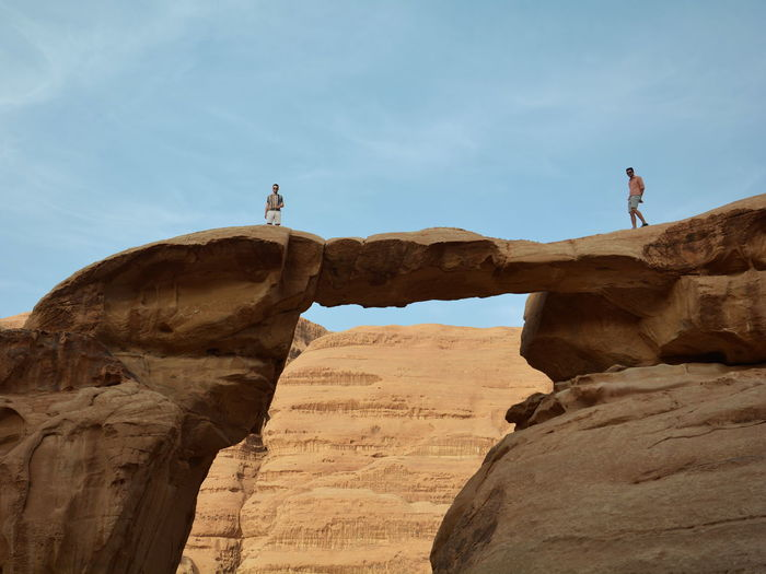 Low angle view of man standing on rock formation against sky in desert