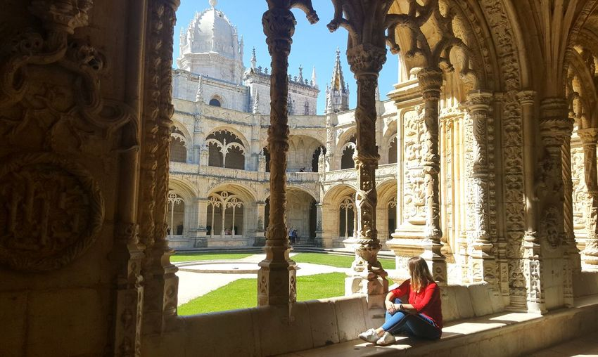 Woman Sitting In Corridor Of Historic Building