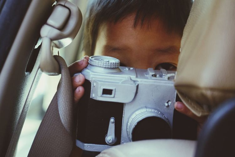 Close-up portrait of boy photographing in car