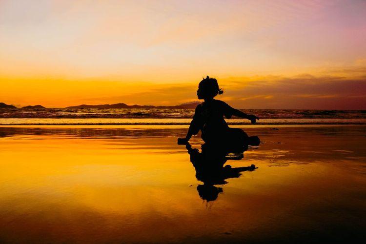 Silhouette girl sitting on beach against sky during sunset