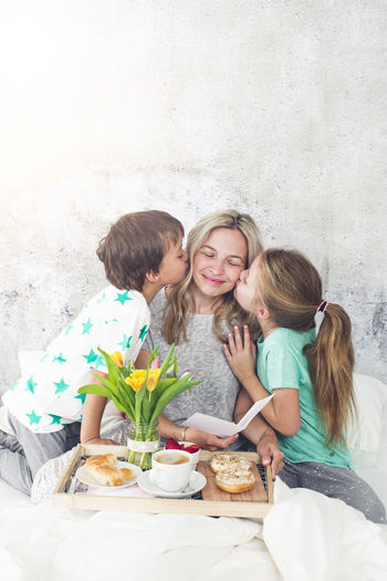 Children kissing mother while having breakfast on bed