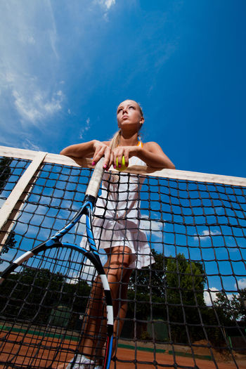 Beautiful woman in a white suit and tennis racket in her hands standing behind the net. Bottom view Effort Outdoors Tennis Ball Young Adult Blue Competition Lifestyles Net - Sports Equipment Athlete Racket Tennis Racket Day Tennis Nature Full Length Front View Sky Low Angle View One Person Sport Real People Leisure Activity Clothing