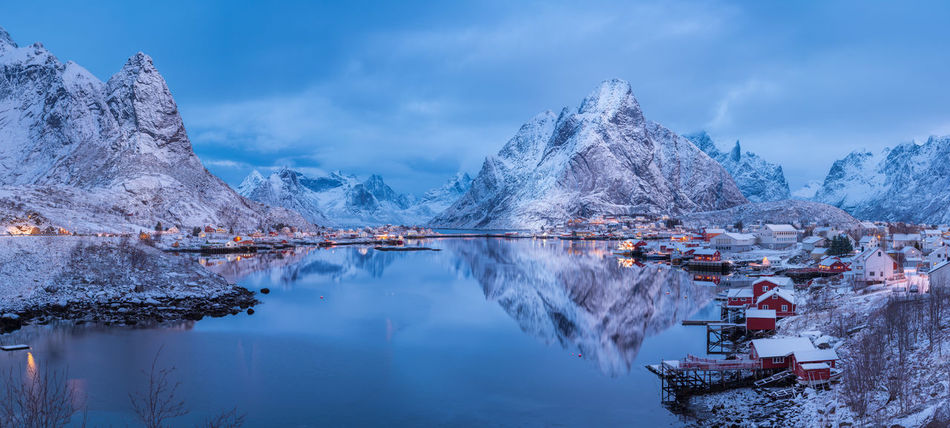 Village of Reine at dawn just after a light snow storm capture in high resolution panorama Archipelago Calm High Resolution Norway Panorama Reflection Reine Serenity Stunning Tranquility Arctic Blue Sky Boats Clouds Fishing Fishing Boat Lofoten Mountain Mountain Range Peaceful Snow Tranquil Scene Travel Destinations Water