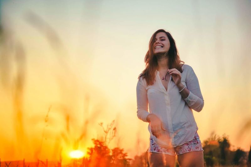 Portrait of a smiling young woman in field during sunset