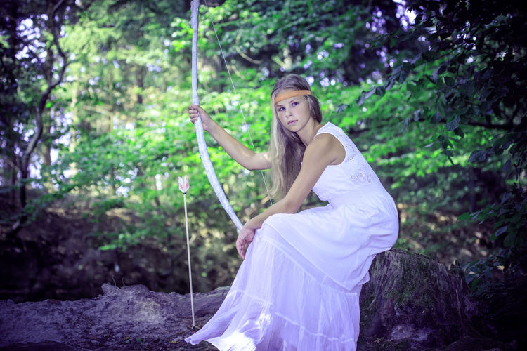 A young amazon with a bow in the rainforest, Book cover style Lamp, Movie, Scary, Castle, Cave, Cute, Dark, Face, Female, Girl, Horror, Human, Light, Lost, Model, Nature, Night, Outdoor, Person, Portrait, Sensuality, Twilight, Walking, White, Young