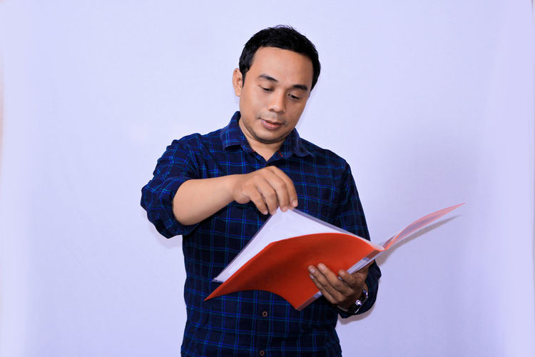 Portrait of a young Asian employee checking documents files One Person Holding Standing Front View Studio Shot Indoors  Casual Clothing Men Young Adult Young Men