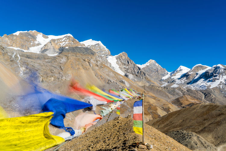 Flags flying by mountains against clear blue sky