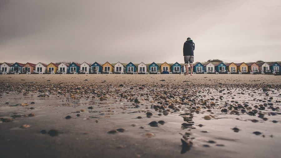 Surface level view of man standing at beach against huts