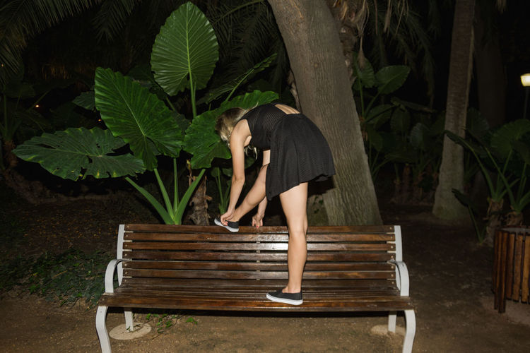 Rear view of woman on bench in park