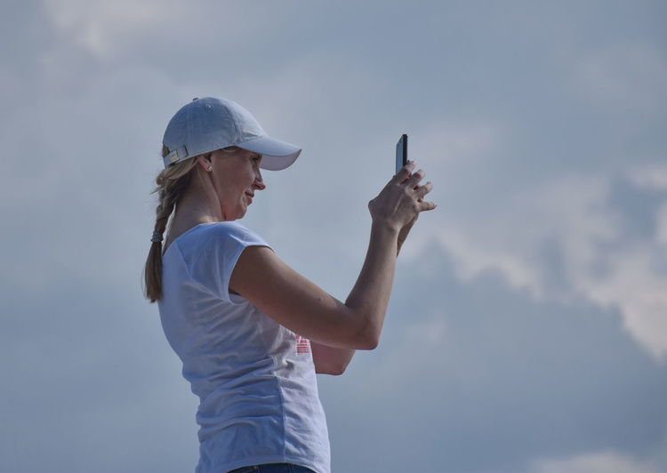 Mobile Phone Taking Photo Adult Casual Clothing Cloud - Sky Communication Day Females Hairstyle Hat Holding Leisure Activity Lifestyles Nature One Person Outdoors Profile View Side View Sky Standing Waist Up Women Young Adult Young Women