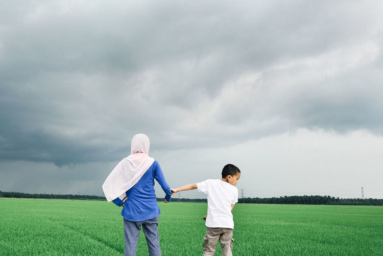 Woman wearing hijab standing with son on grassy field against storm clouds
