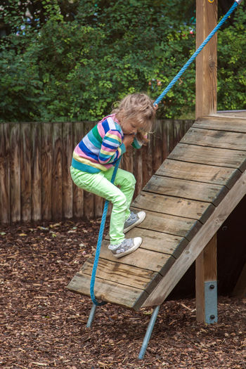Girl climbing with rope on outdoor play equipment