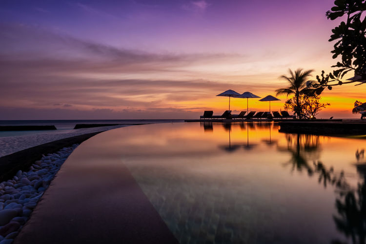 Scenic view of swimming pool against dramatic sky during sunset