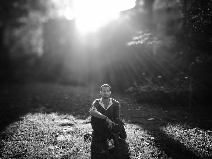 Portrait of young man sitting on field during sunny day