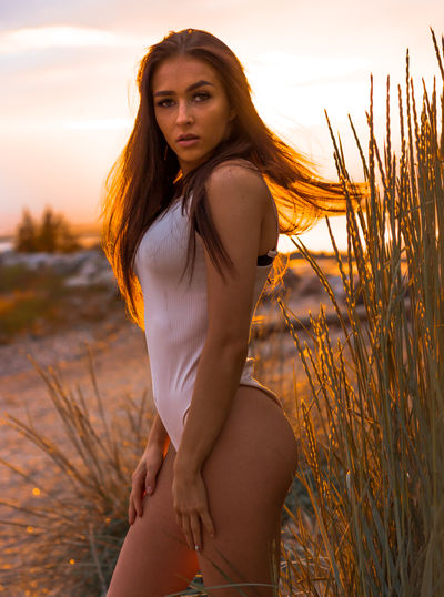 Portrait of beautiful young woman standing at beach during sunset