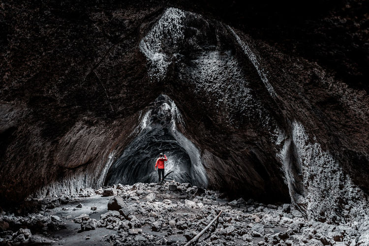 Rear view of person standing in cave