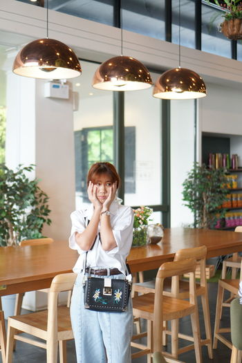 Worried young woman touching her cheeks while sitting in restaurant