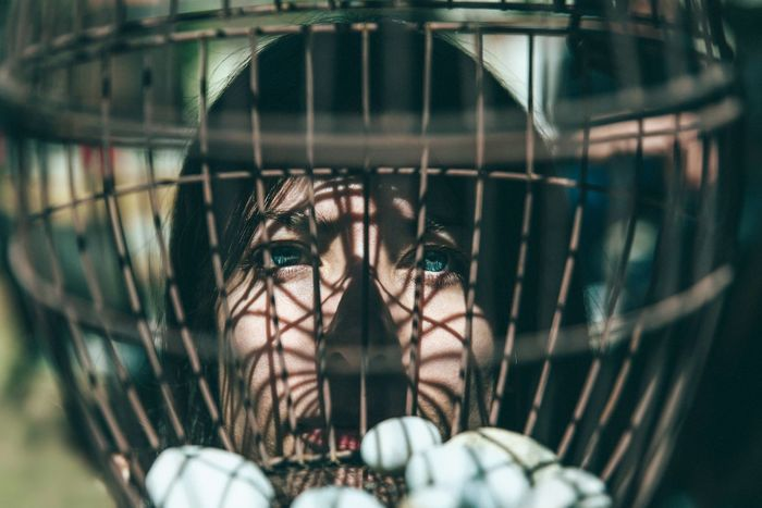 Close-up portrait of young woman seen through cage