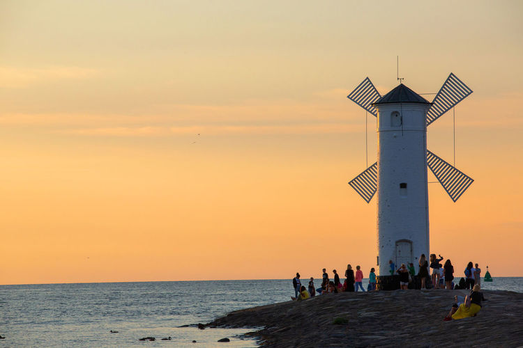 Baltic Sea Stawa Mlyny Architecture Beach Beauty In Nature Building Building Exterior Built Structure Group Of People Horizon Horizon Over Water Land Nature Orange Color Outdoors Real People Scenics - Nature Sea Sky Sunset Tower Water