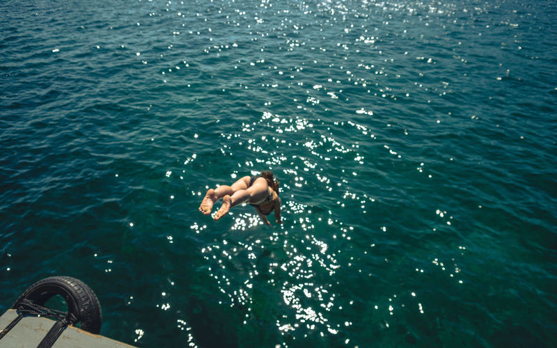High Angle View Of Woman Diving Into Sea