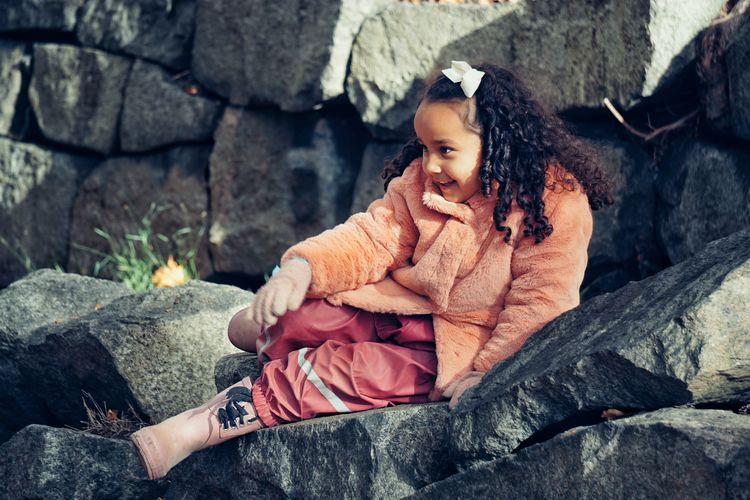 Full length of girl sitting on rock